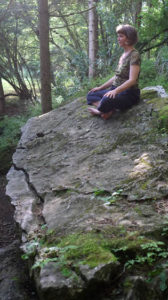Nina in yoga position on a rock in the forest